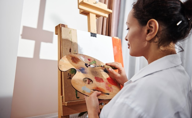 Winkelansicht eines lächelnden brünetten malers, der eine palette mit ölfarbe und einem farbmesser in den händen hält, die vor einer staffelei stehen