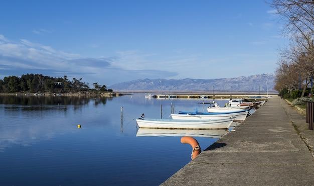 Winkelaufnahme eines sees mit angedockten booten unter einem blauen himmel