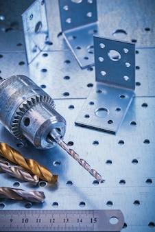 Winkelbefestigungsbits lineal und metallbohrer auf perforiertem metallischem hintergrundkonstruktionskonzept