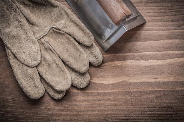 Winkelformer mit schutzhandschuh auf holzbrett.