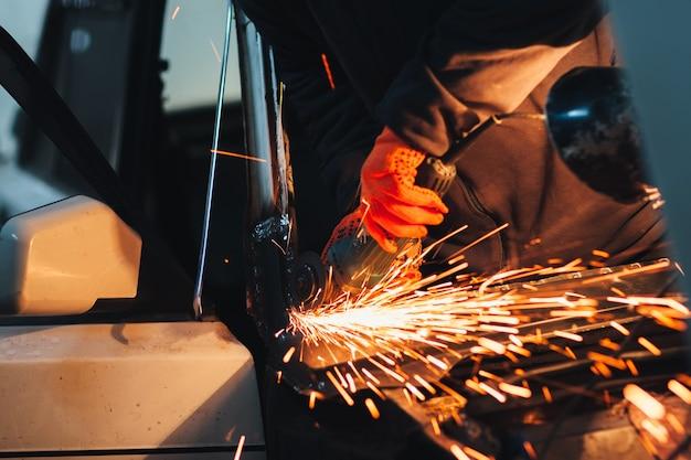 Winkelschleifer-blitzherstellung durch arbeiter in der garage