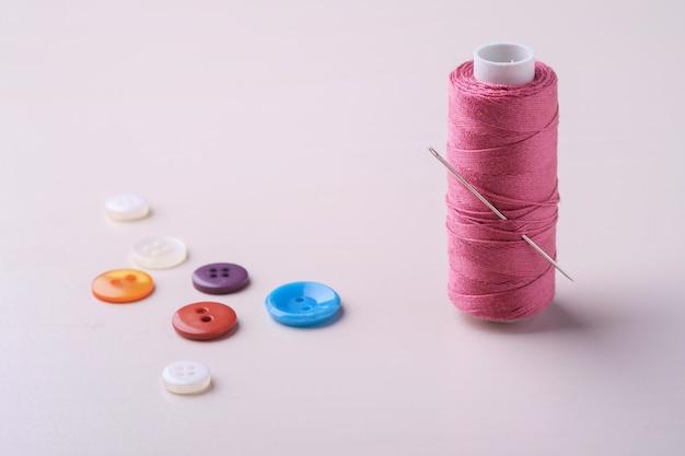 Winkelsicht nah oben von der rosa threadspule mit knöpfen und nadel