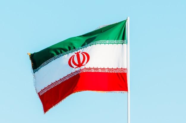 Winkende bunte iranflagge auf blauem himmel.