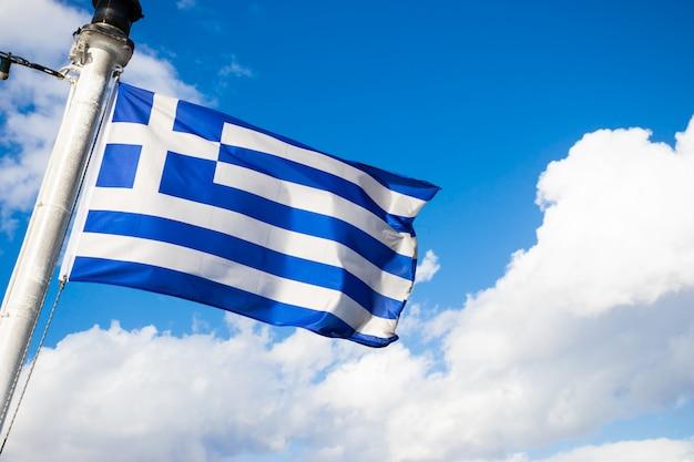 Winkende griechische flagge an einem sonnigen tag gegen den himmel