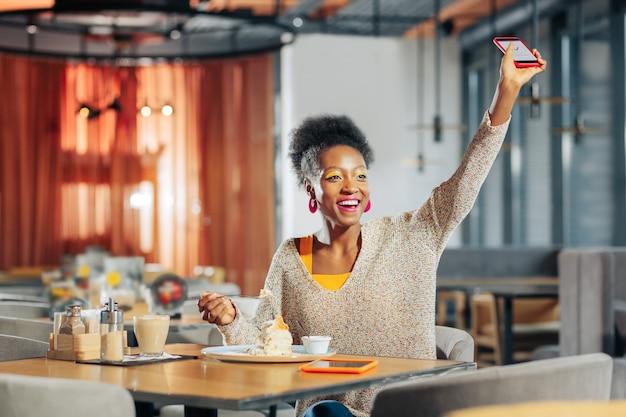 Winkender freund positive afroamerikanerin mit hellem make-up, die ihren freund im restaurant winkt