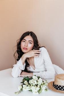 Winsome asiatische frau mit weißen blumen, die kamera betrachten. studioaufnahme der attraktiven chinesischen frau mit strauß von eustomas.