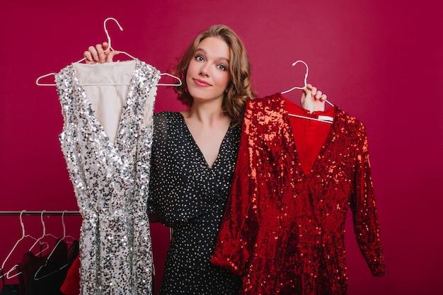 Winsome brünette frau, die kleiderbügel mit funkelnden partykleidung hält
