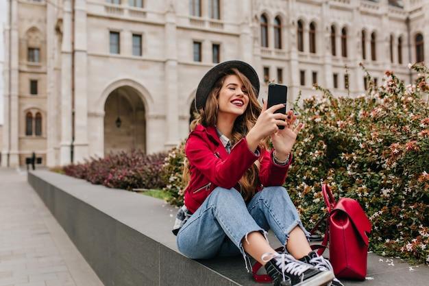 Winsome frau in den sportschuhen, die auf der straße mit smartphone sitzen und lächeln