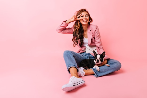 Winsome junge dame mit langen haaren, die auf dem boden mit hund aufwerfen. erstaunliches brünettes mädchen, das auf rosa mit französischer bulldogge sitzt.