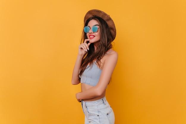 Winsome junge frau in der stilvollen funkelnden brille, die auf gelbem raum aufwirft