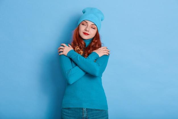 Winsome junge romantische frau mit rotem welligem haar drückt selbstliebe und fürsorge aus
