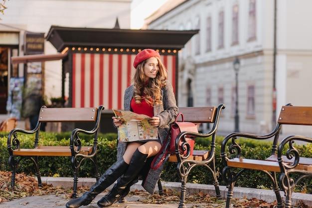 Winsome kaukasische frau in den kniehohen schuhen, die im park mit stadtplan sitzen