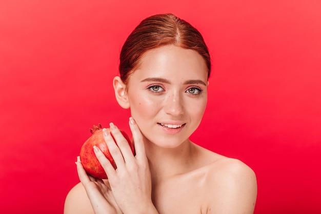 Winsome mädchen, das granat mit sanftem lächeln hält. studioaufnahme der erstaunlichen ingwerdame mit frucht lokalisiert auf rotem hintergrund.