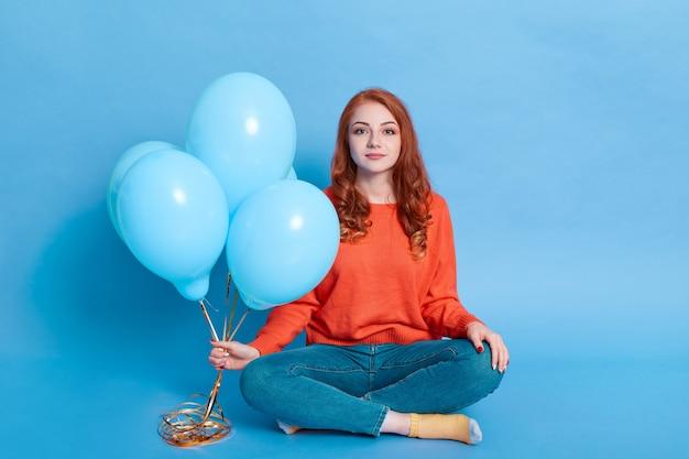Winsome mädchen gekleidet in freizeithemd und jeans hält luftballons in ihren händen, während auf boden isoliert über blauer wand sitzen
