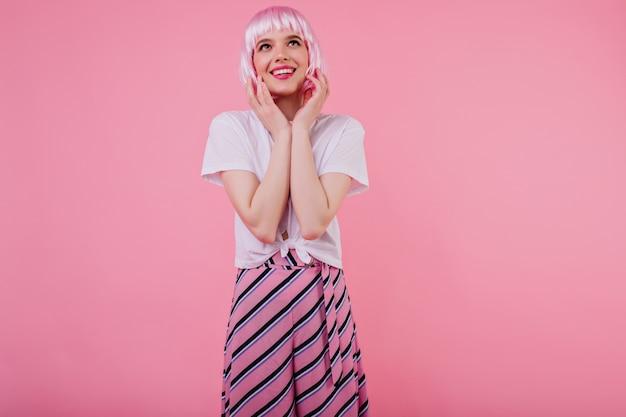 Winsome mädchen in der guten laune, die auf rosa wand in peruke aufwirft. innenfoto der fröhlichen europäischen dame in der glamourösen kleidung, die während des fotoshootings lächelt