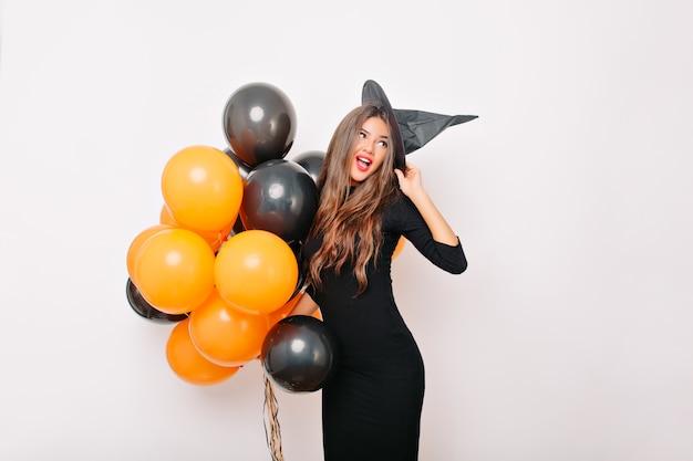 Winsome schlanke frau, die mit bunten luftballons aufwirft