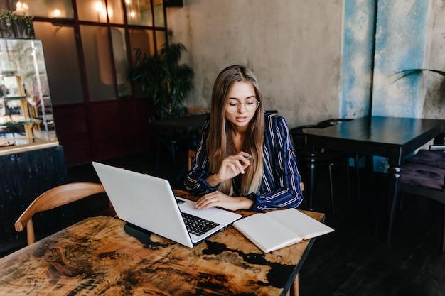 Winsome weibliche sekretärin, die mit computer arbeitet. innenaufnahme des reizenden kaukasischen studenten, der laptop für hausaufgaben verwendet.