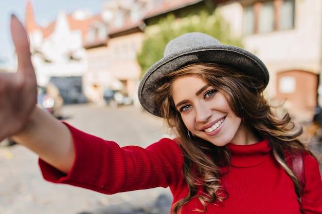 Winsome weiße frau im gestrickten pullover, der selfie beim gehen auf allee macht