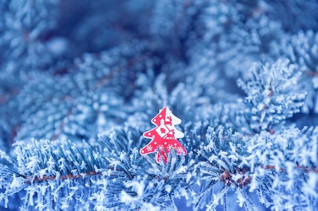 Winter, abschluss oben des bereiften kiefernzweigs an einem schneienden tag