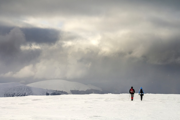 Winter berglandschaft. hintere ansicht von touristischen wanderern der reisenden mit rucksäcken auf dem schneebedeckten feld gehend in richtung zum entfernten berg
