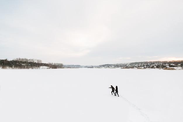 Winter. der kerl und das mädchen gehen auf einen winter verschneiten gefrorenen see.