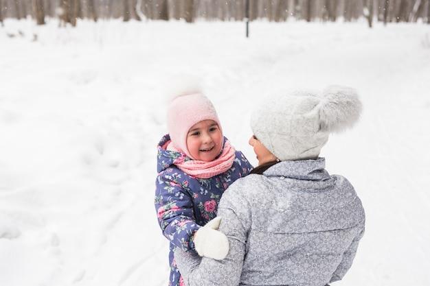 Winter-, familien- und kindheitskonzept - mutter geht mit ihrer tochter im verschneiten wald spazieren und