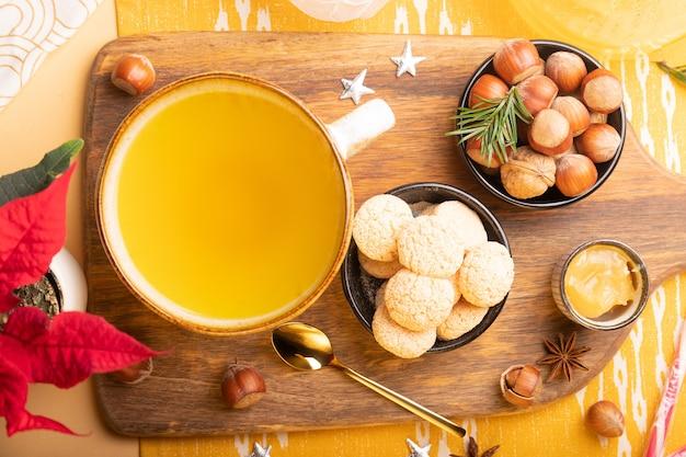 Winter flach mit ingwertee, keksen, nüssen und weihnachtsdekoration auf dem tisch