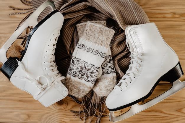 Winter flatlay mit weißen schlittschuhen zum eiskunstlauf, einem warmen schal und handschuhen