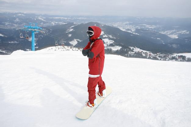 Winter-, freizeit-, sport- und menschenkonzept - nahaufnahme eines snowboarders, der auf seinem board mit blick auf eine skipiste auf dem schneebedeckten hang unten in einem wintersportort steht