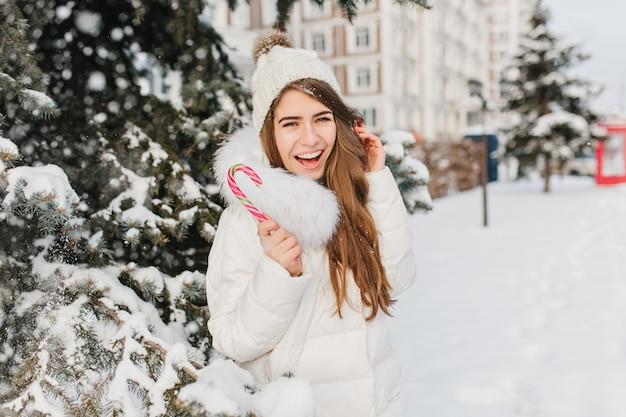 Winter gefrorene zeit der lustigen erstaunlichen frau, die spaß mit rosa lollypop auf der straße hat. junge freudige frau, die in der warmen jacke, in der strickmütze schneit, die positivität ausdrückt. leckere, süße winterzeit.