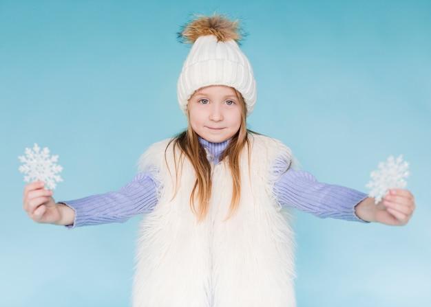 Winter gekleidetes kleines mädchen, das schneeflocken hält