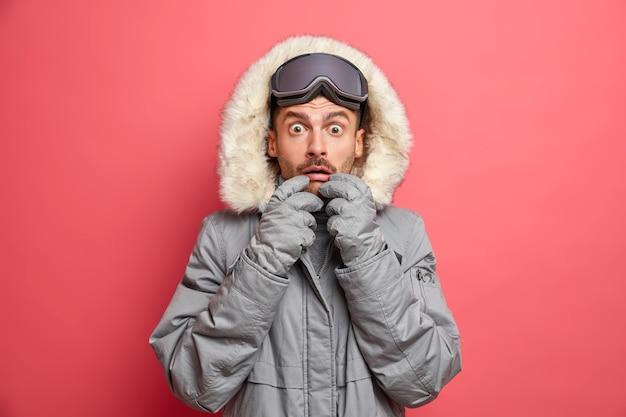 Winter hobby und erholungskonzept. besorgter unrasierter kaukasischer mann starrt in oberbekleidung gekleidete augen an, trägt eine snowboardbrille und findet schockierende neuigkeiten heraus.