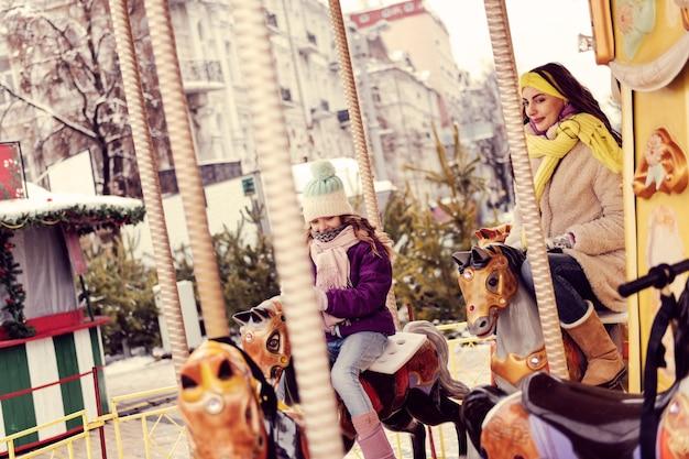 Winter in der stadt. erfreutes mädchen, das warmen hut trägt, während es draußen ist