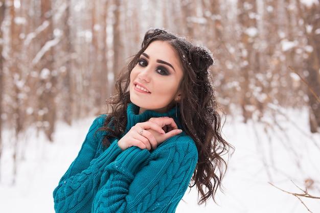 Winter-, jahreszeit- und personenkonzept - nahaufnahmeporträt der jungen hübschen frau, die im verschneiten park geht