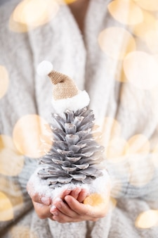 Winter-konzept-junge hände, die weihnachtsdekor halten. weihnachtsdekoration idee. weihnachtsdekor in den händen einer frau, hintergrund mit goldenem bokeh. Premium Fotos