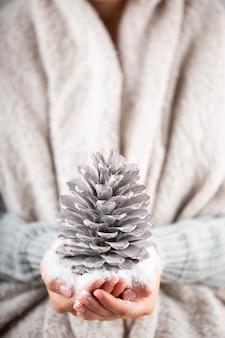 Winter-konzept-junge hände, die weihnachtsdekor halten. weihnachtsdekoration idee. weihnachtsdekor in den händen einer frau, hintergrund mit goldenem bokeh.