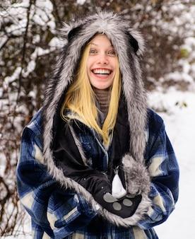 Winter. lächelnde frau in warmer kleidung mit schneeball. mädchen, das mit schnee spielt. jahreszeit des winters.
