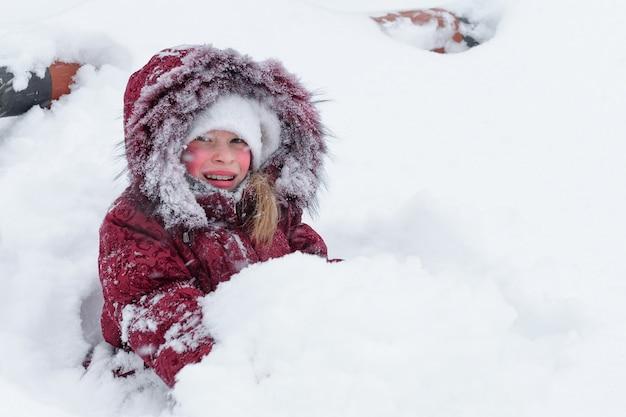 Winter. mädchen, das mit schnee im schnee spielt.