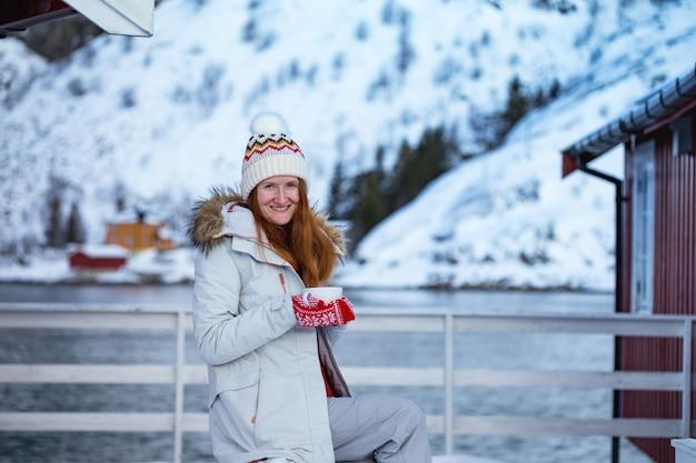 Winter. mädchen mit einer tasse auf dem hintergrund des rorbu auf den lofoten. norwegen