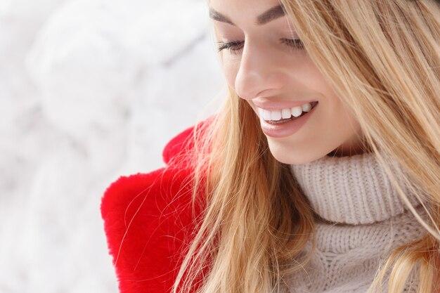 Winter, mode, menschen konzept - mode porträt einer schönen jungen frau spaziergänge durch die stadt lächelnd roten pelzmantel close-up schneeflocken kalten winter, frische luft am frost wintertag atmen. sonnenuntergang