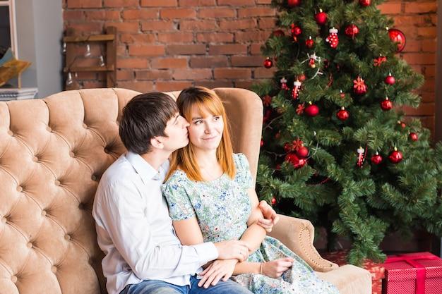 Winter-, mode-, paar-, weihnachts- und personenkonzept - lächelnder mann und frau, die über weihnachtsbaum umarmen