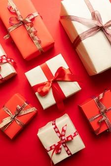 Winter, neujahrskonzept. kreative zusammensetzung der geschenkbox mit gold spielt dekoration, bälle auf rotem hintergrund die hauptrolle. flache lage, draufsicht, kopienraum