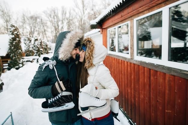 Winter. paare in der warmen winterkleidung mit rochen gehen zur eisbahn.