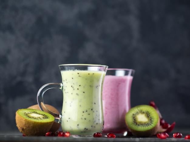 Winter saisonale smoothie getränke entgiftung. zwei gläser grüne und rote smoothies. kiwi und granatapfel hausgemachter joghurt. konzept für gesunde ernährung