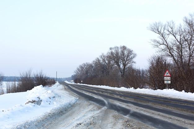Winter schlecht geräumte straße. straße auf dem lande mit schnee übersät. schneeverwehungen