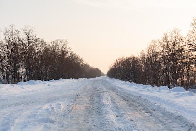 Winter schlecht geräumte straße. straße auf dem lande mit schnee übersät. winterlandschaft mit schneeverwehungen