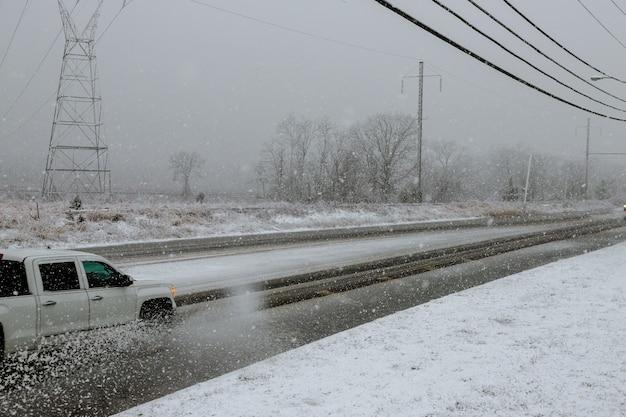 Winter, schnee, blizzard, schlechte sicht auf der straße. auto während eines blizzards auf der straße