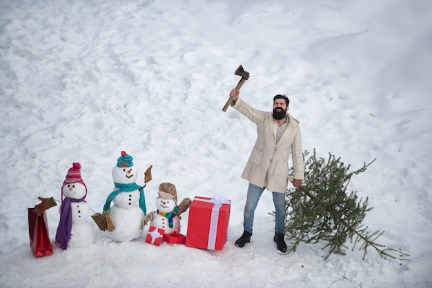 Winter schneemann landschaft. aufgeregter holzfäller trägt tannenbaum auf dem schneemannhintergrund. thema
