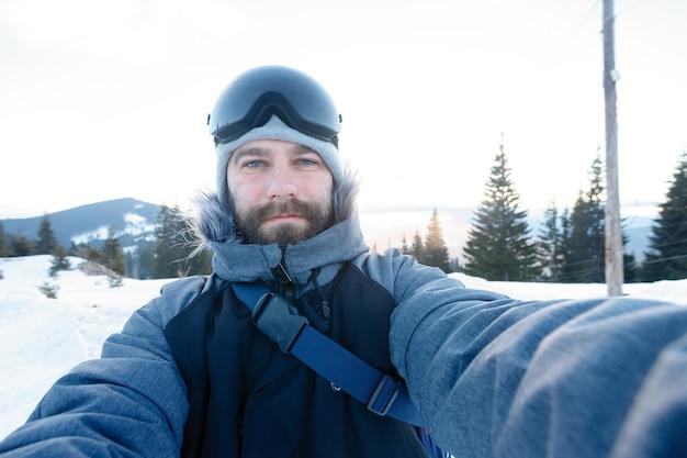 Winter-, sport- und menschenkonzept - freerider-snowboarder, der auf einem steilen hang des berggipfels steht und ein selfie-porträt mit kamera oder smartphone auf dem hintergrund der schneebedeckten berge im skigebiet macht