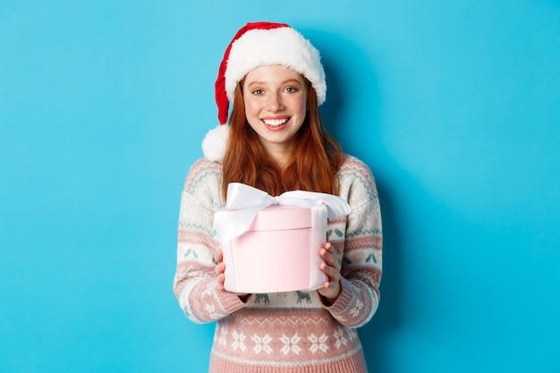 Winter- und feierkonzept. entzückendes rothaariges mädchen, das ihnen ein geschenk gibt, frohe weihnachten wünschend, stehend ich weihnachtsmütze gegen blauen hintergrund.